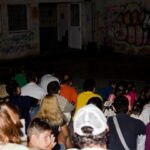 crowd watching projection on old building