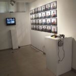 Tv with Video, grid of photographs on wall and pedestal with blocks and headphones