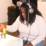 woman with headphones on building with blocks
