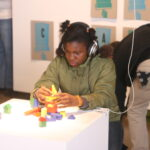 girl with headphones on building with blocks