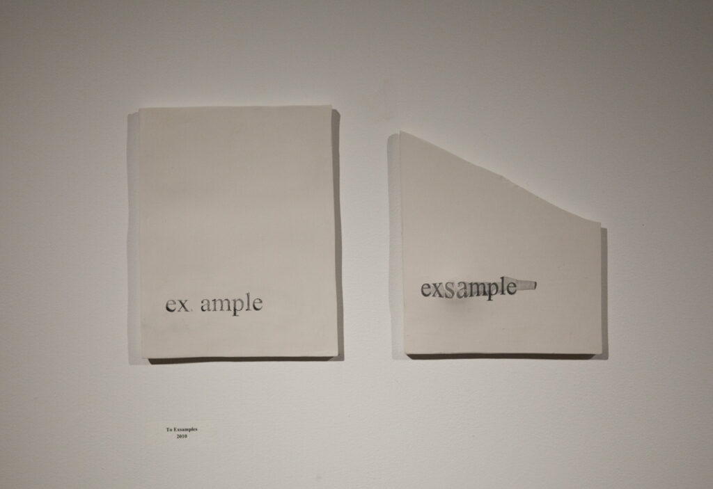 2 ceramic pages on wall one says E ample one says EXSAMPLE