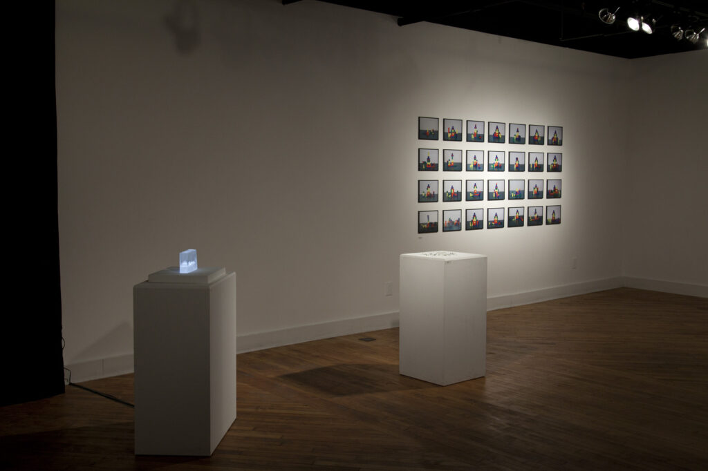 empty gallery full of art, grid of photos on the wall, two sculptures on pedestals