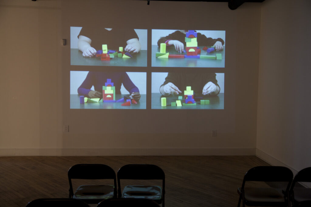 empty gallery full of art, projection of video on wall