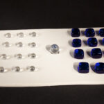 white game board similar to a chess set, set of pieces on left clear round glass, set on let blue glass squares, no move on the board, one piece blue and clear marble sits in the middle unable to move