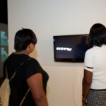 two woman standing watching a video with wall projection in background