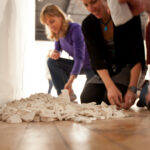people kneeling on the floor gathered around ceramic tiles with letters on them