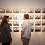 woman and man looking at grid of photographs on wall