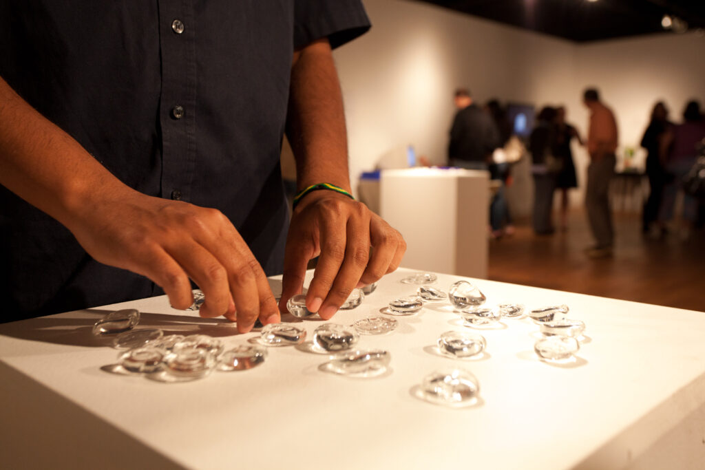 hands touching glass letters