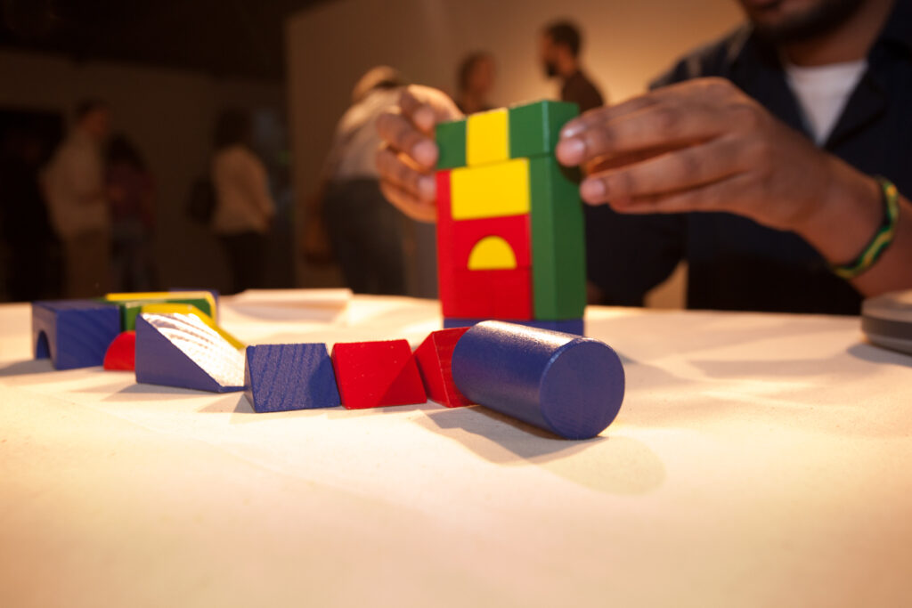 close up of hands building with multicolored blocks