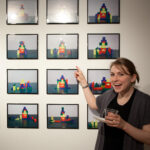 woman pointing to photographs on the wall