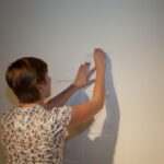 woman hanging a page of text on the wall