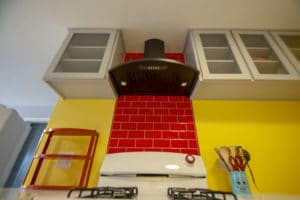 Candy apple red backsplash above oven with black hood and glass door cabinets