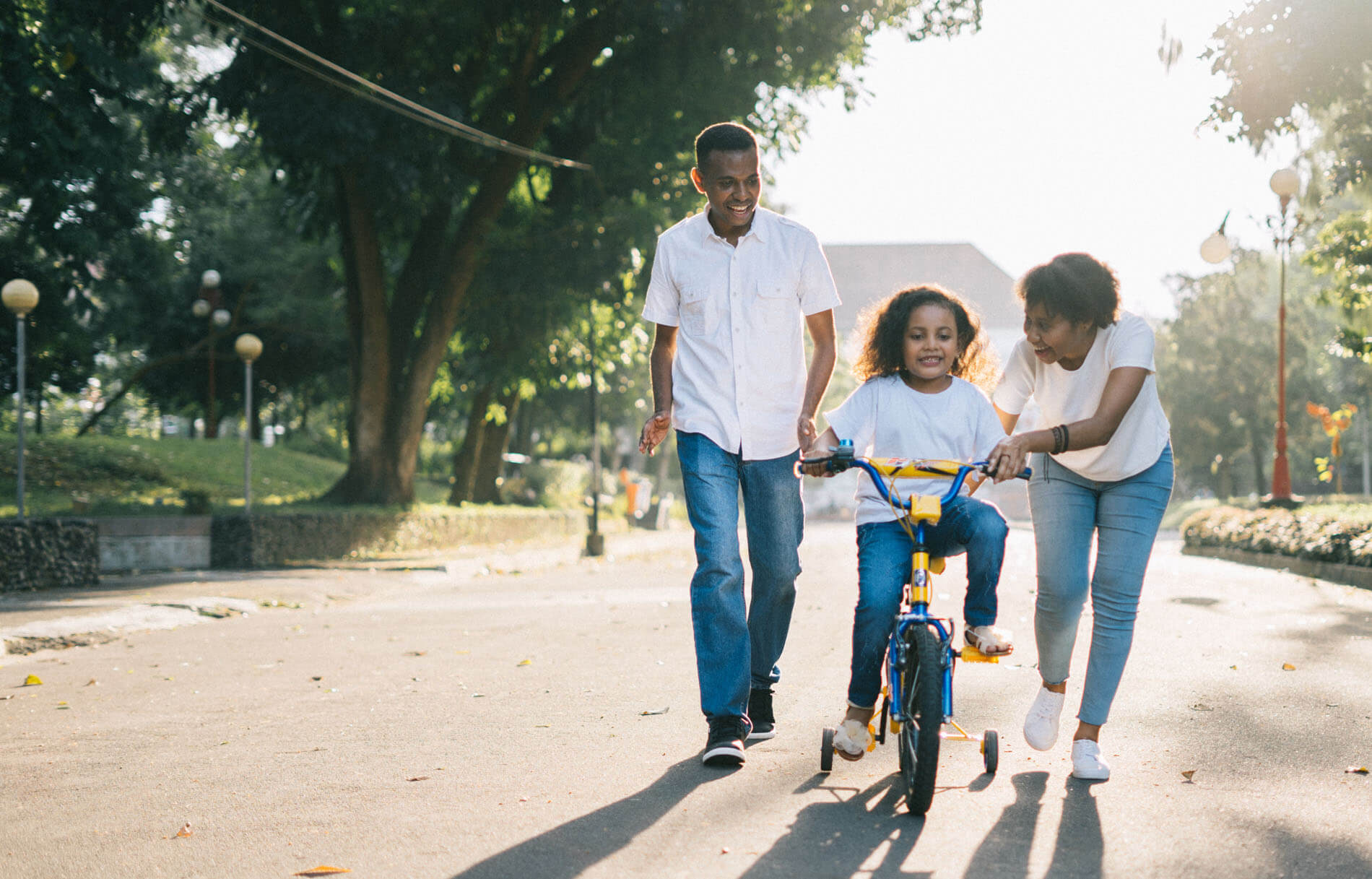 An image of a family with young daughter learning to ride a bike.