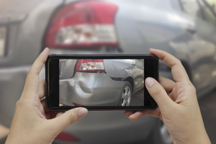 Person taking picture of fender bender for auto body repair estimate