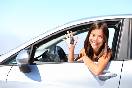 Smiling girl in car window with keys