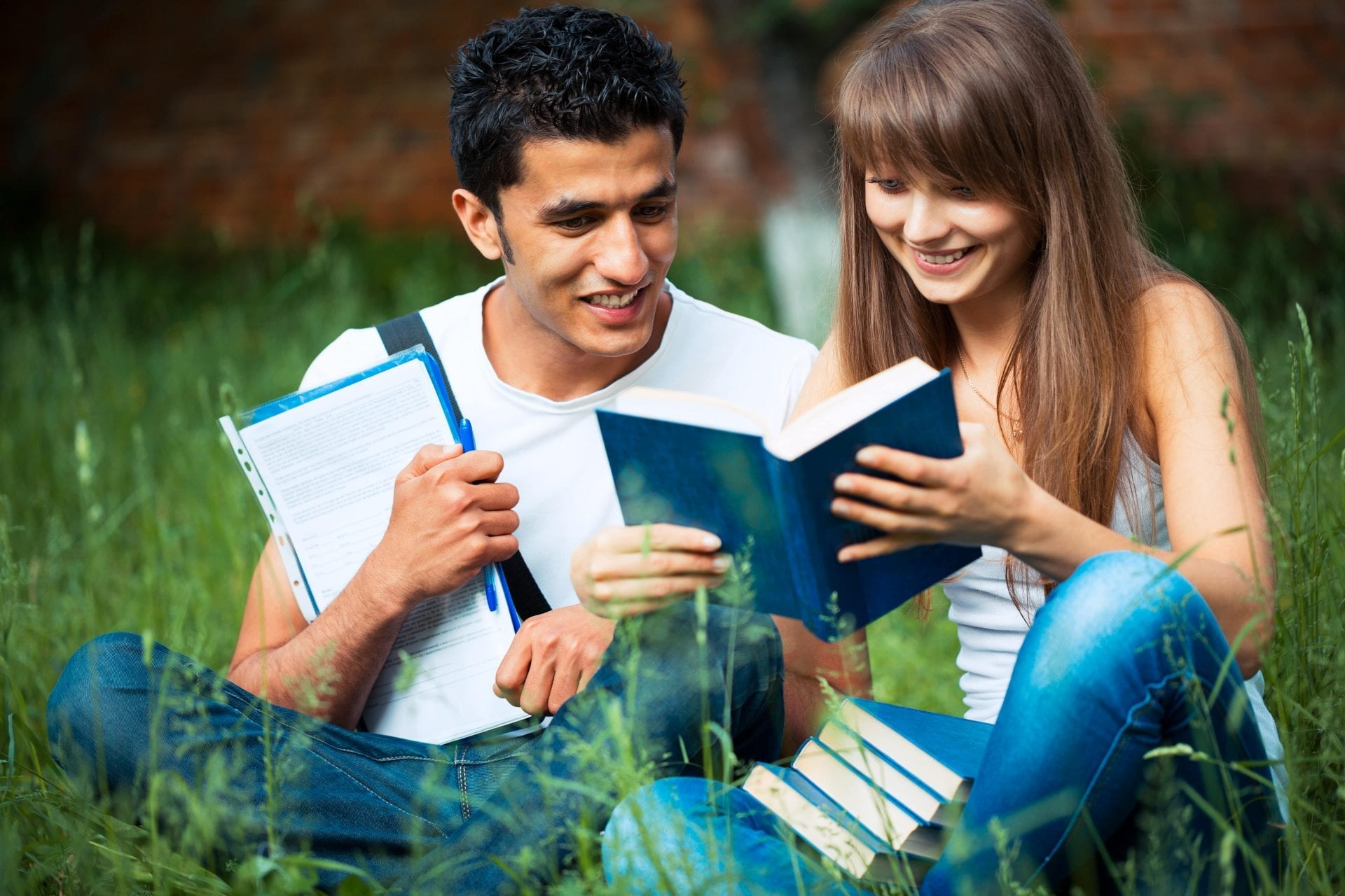 two-students-studying-in-park-on-grass-PD68WLH-min