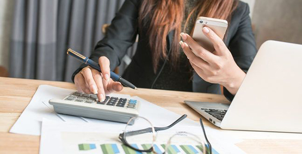 Woman calculating budget on phone and laptop