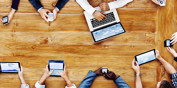 Business people using different technology seated around a table