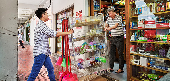 Two men pulling product rack inside store