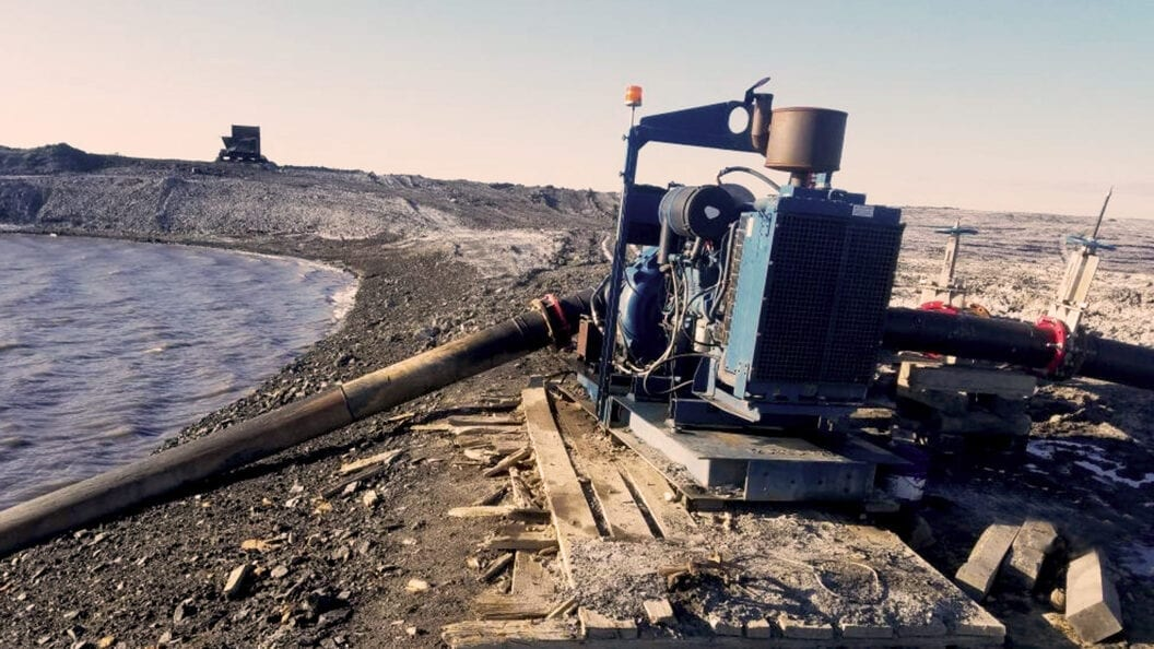 Dewatering pump moving water at a mining site.
