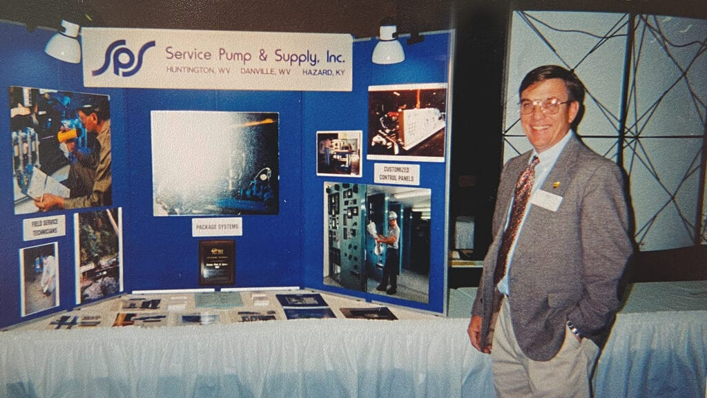 Photo: Dave Crabtree, founder of SPS's municipal solutions division, poses in front of a Service Pump trade show booth circa 1985.