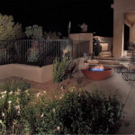 Gas fire bowl at edge of colored exposed aggregate concrete patio