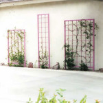 Ornamental iron trellises on garage wall at entry drive
