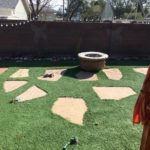 Patio with worn turf and flagstone.
