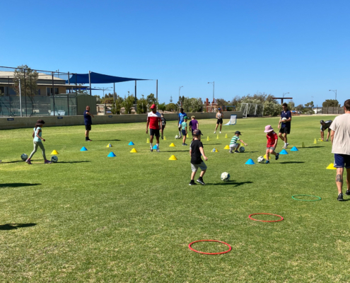 Coaches and children playing football.