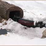 Garden Railroad making its way throught he snow and through the big log in the Train Garden.