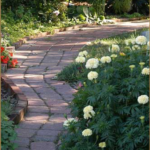 Pathway in Romance Garden. Winding pavers of red stone and lush plantings on either side.