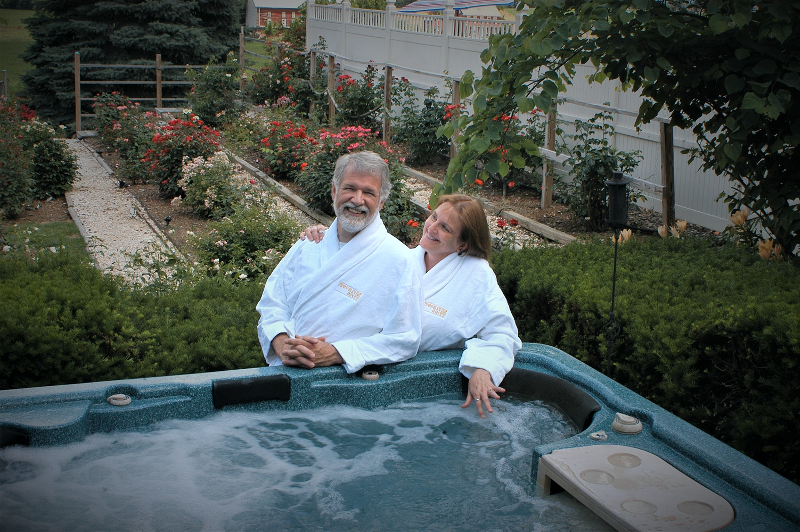 Couple by hot tub in Annville Inn Robes. Part of Rose Garden in background.