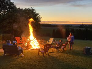 A group of people sitting around a bonfire near sunset with Pennsylvania countryside in the background.