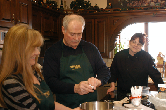 Chef observes two students working on project during Acclaimed Chef Cooking Class.