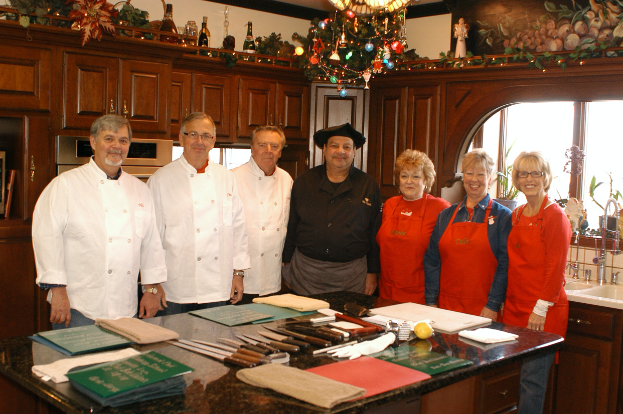Chef in black chef's outfit with six students he is teaching. The men are wearing white cooking jackets and the women red aprons. Acclaimed Chef Cooking Class, Annville Inn.