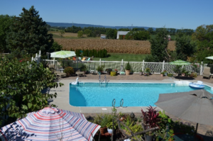Swimming Pool with farms and mountains in background.