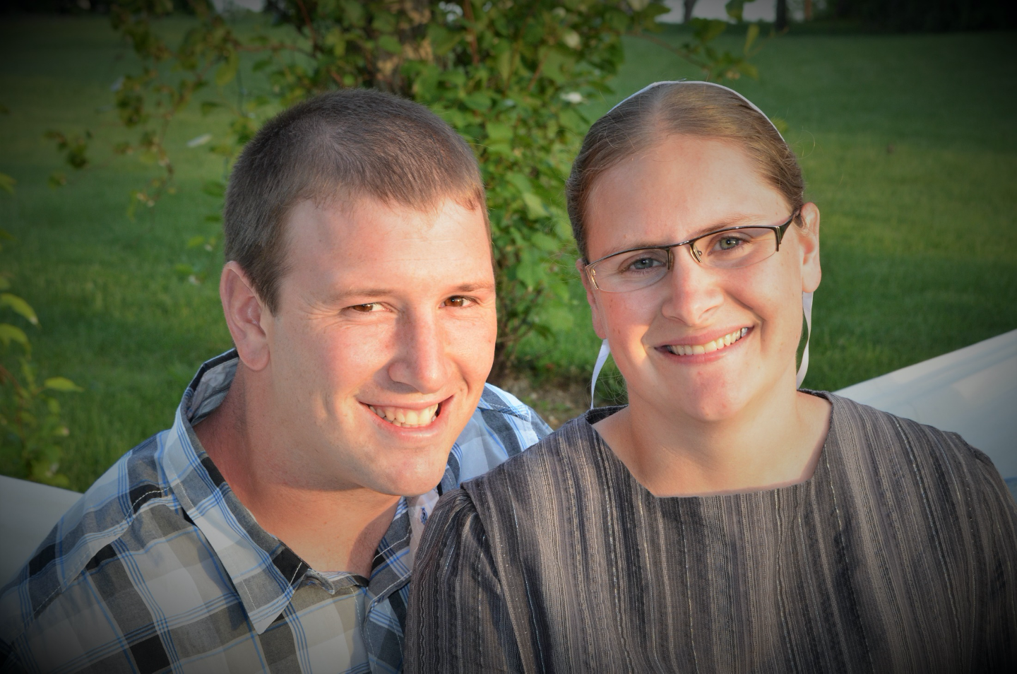 Professional portrait of young Mennonite couple outdoors.