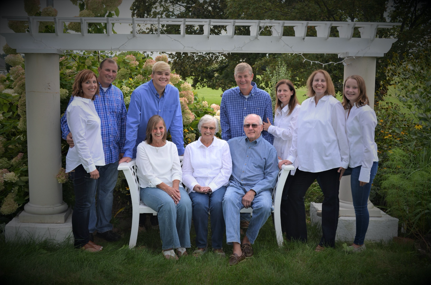 Portrait of family of ten wearing blue and white clothing, outdoors under a pergola.