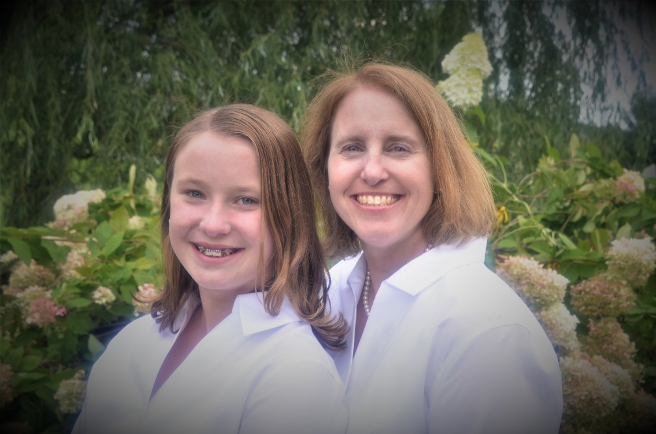 Portrait of mother & daughter outdoors.