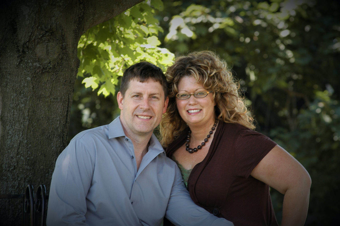 Professional portrait of couple outside under tree, light filtering through leaves in background.