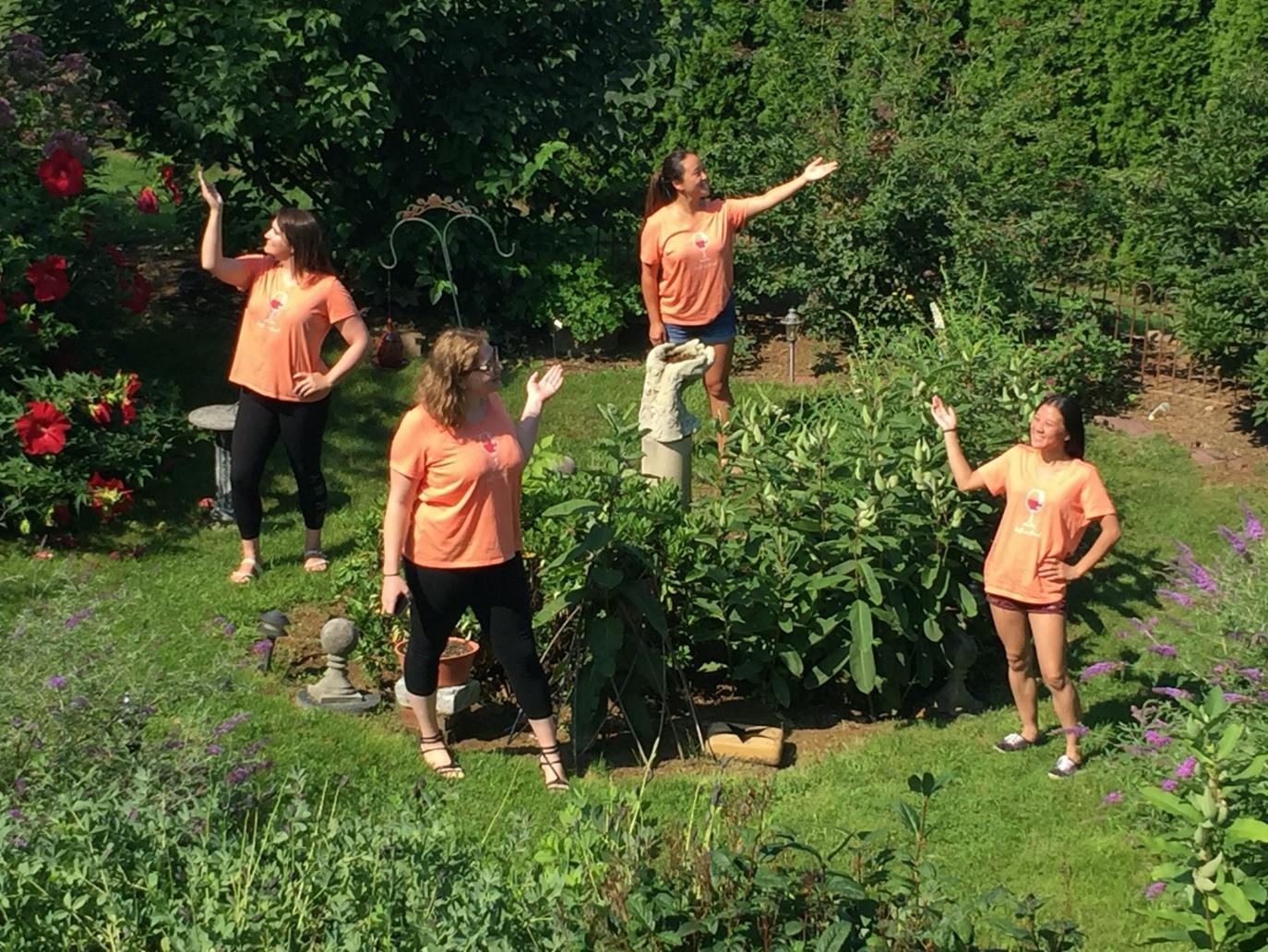 Group of four young ladies in statue garden enjoying friends' retreat. Wearing matching orange tee shirts.