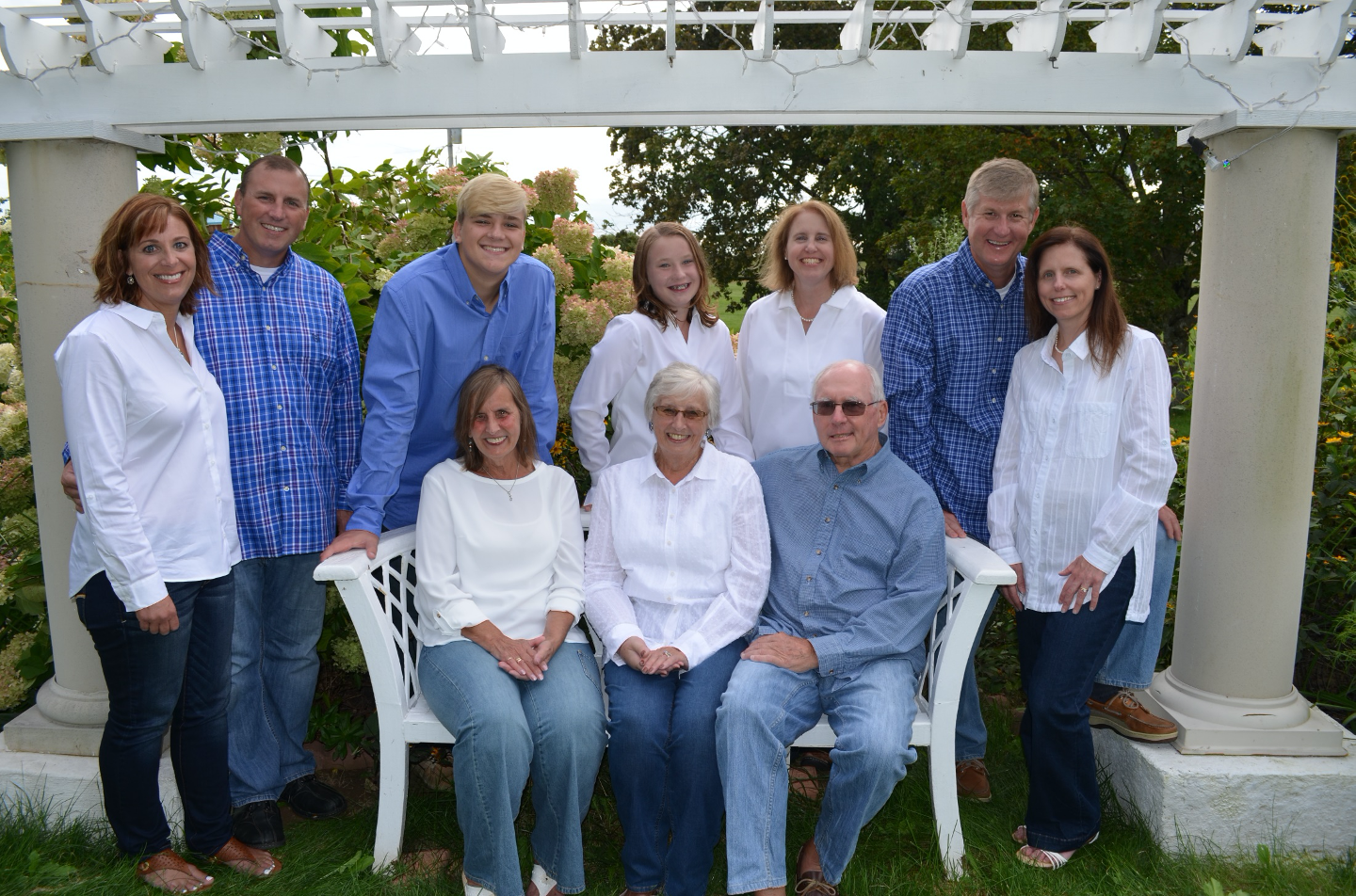 Family Group of of ten outdoors posing for portrait, all wearing blue and white.