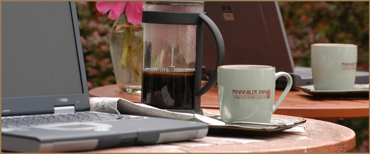 Still life image of newspaper, computer, French Press coffee maker and two Annville Inn coffee mugs.