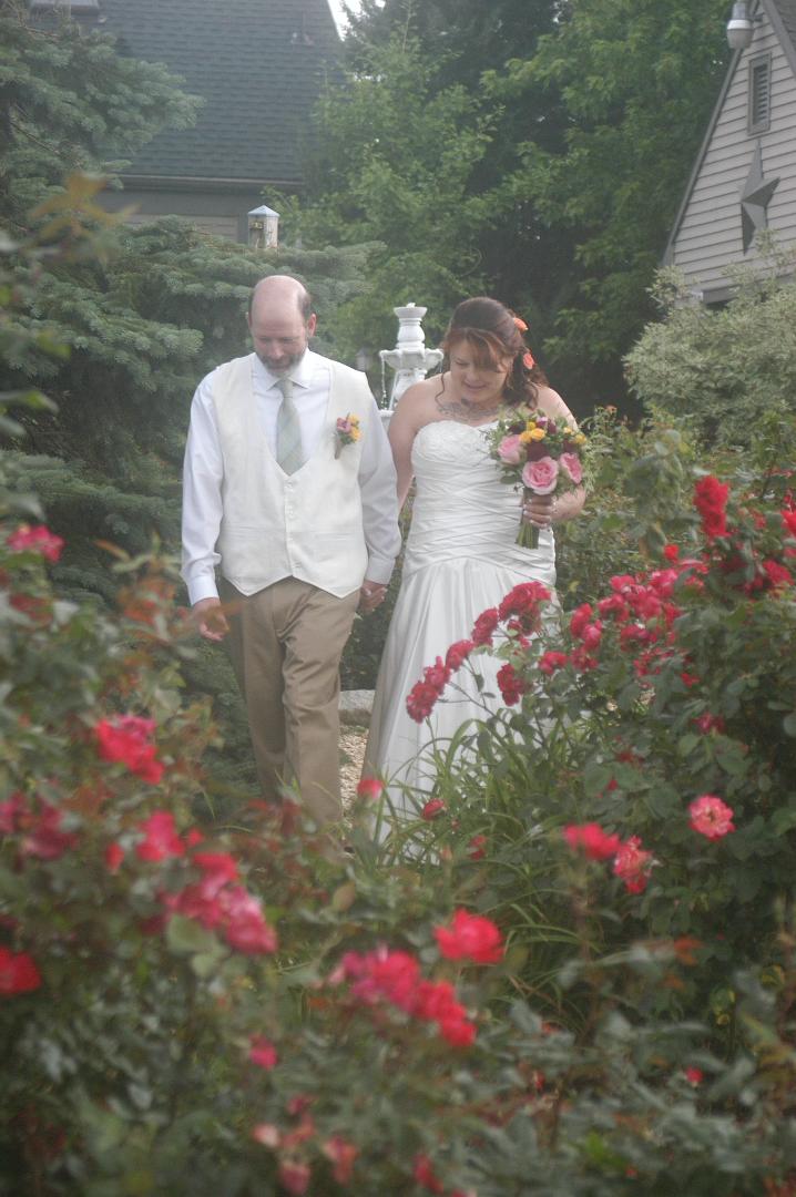 Bride and Groom walking through rose garden at Annville Inn B&B