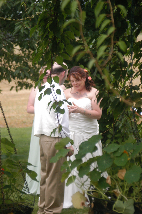 Bride and groom exchanging rings at outdoor wedding in the Pergola Garden