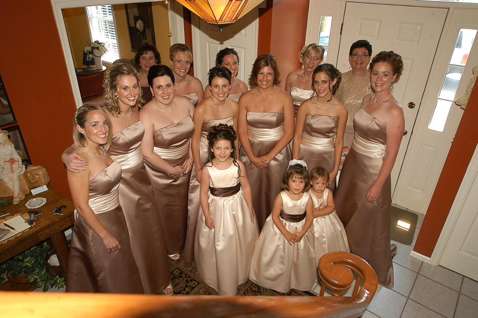 Group of Bride's Maids awaiting bride at foot of stairs
