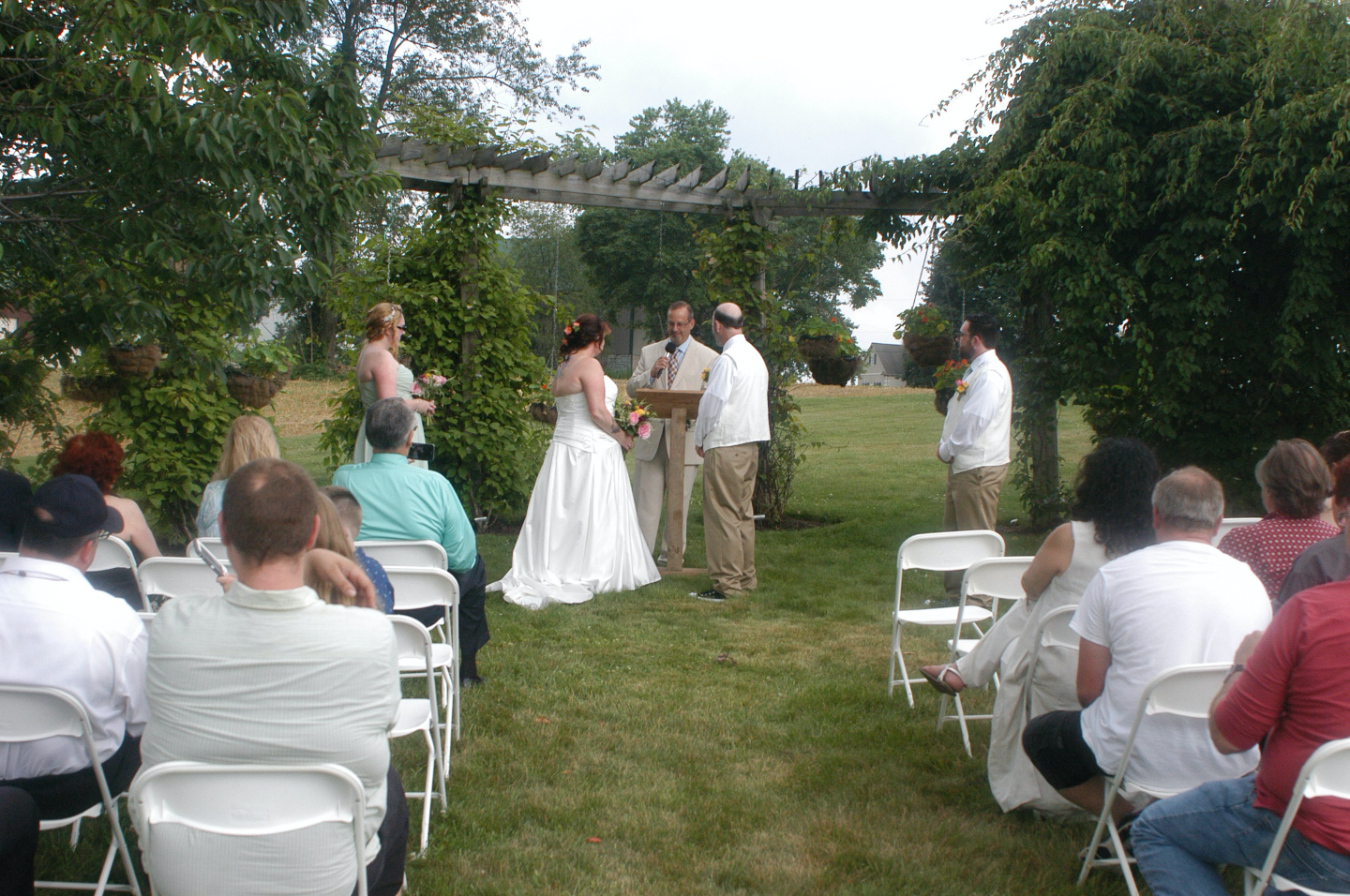Bride and groom exchanging vows at Pergola Garden