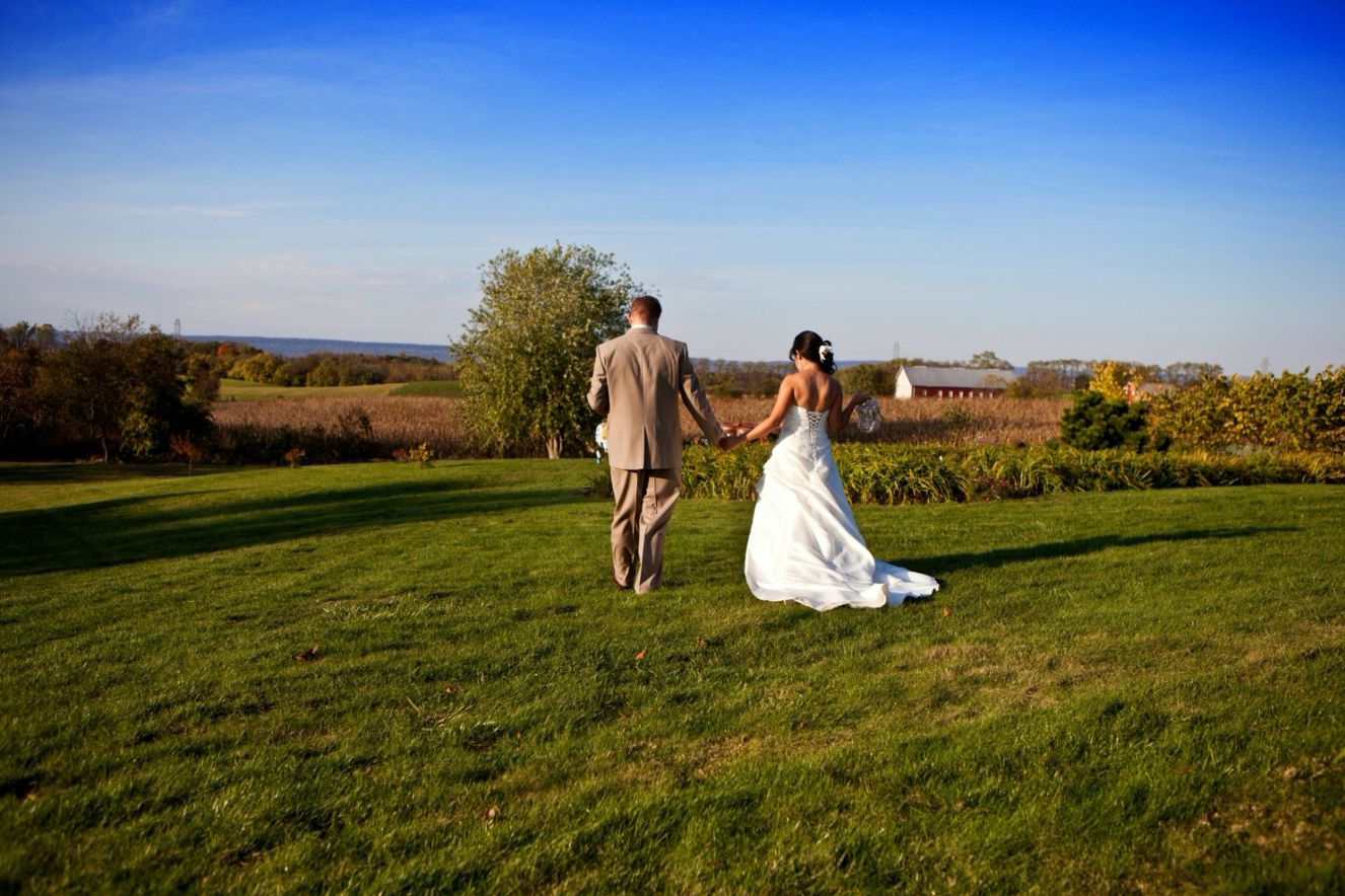 Bride and Groom walking through lawn toward old farmstead in background. Further back, the Blue Mountains and the blue sky.