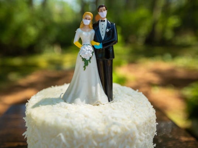 Caketop showing bride and groom, both wearing face masks.