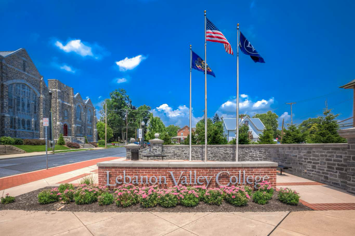 Entrance to Lebanon Valley College. Sign with flags, blue sky in background.